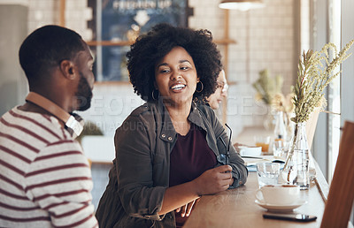 Buy stock photo Shot of young business partners sitting and talking with each other in a coffee shop during the day