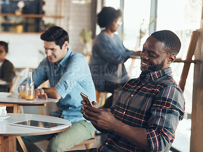 Buy stock photo Shot of a handsome young man sitting in a busy coffee shop while using his cellphone during the day