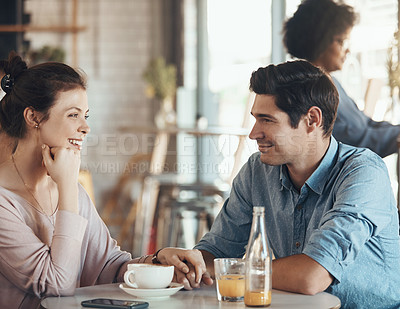 Buy stock photo Shot of an affectionate young couple sitting with each other in a coffee shop during the day