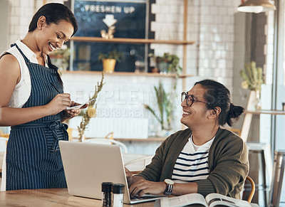 Buy stock photo Shot of a friendly young waitress writing down an order for a handsome young businessman in a coffee shop