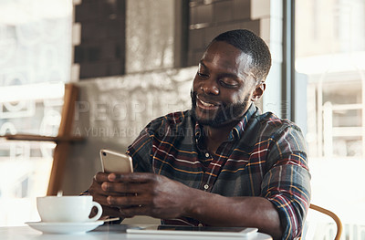 Buy stock photo Shot of a handsome young man sitting and using his cellphone in a coffee shop during the day