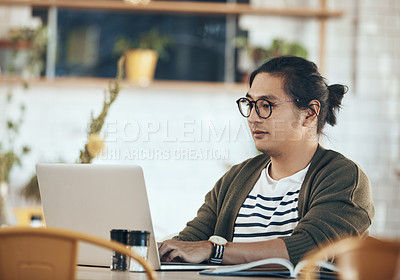 Buy stock photo Shot of a handsome young man sitting and working on his laptop in a coffee shop during the day