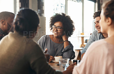 Buy stock photo Shot of a young diverse group sitting together and smiling in a coffee shop during the day