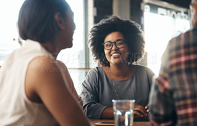 Buy stock photo Shot of attractive young women sitting and smiling with friends in a coffee shop during the day