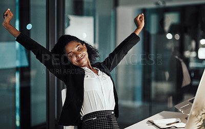 Buy stock photo Shot of a young businesswoman stretching at her desk while working late in an office