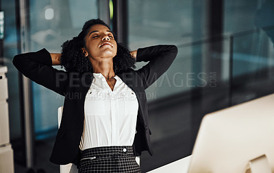 Buy stock photo Shot of a young businesswoman resting with her hands behind her head while working in an office at night