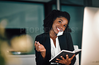 Buy stock photo Shot of a young businesswoman writing notes while talking on a cellphone in an office at night