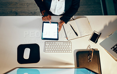 Buy stock photo High angle shot of an unrecognizable businesswoman using a digital tablet while working at her desk in an office at night