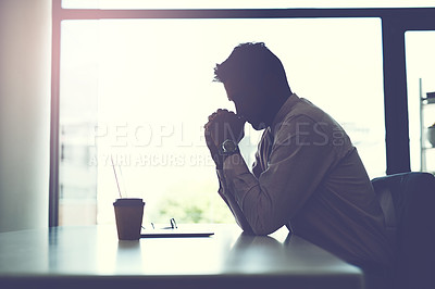 Buy stock photo Shot of a businessman looking stressed while sitting at his desk
