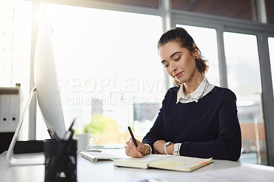 Buy stock photo Shot of an attractive young businesswoman sitting at her desk and writing notes in a modern office
