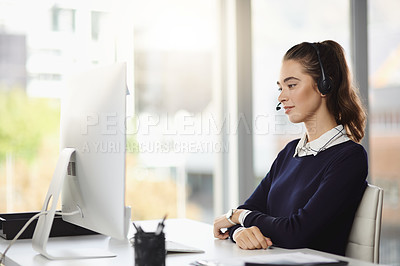 Buy stock photo Shot of a smiling attractive young businesswoman wearing a headset and sitting at her desk in a modern office