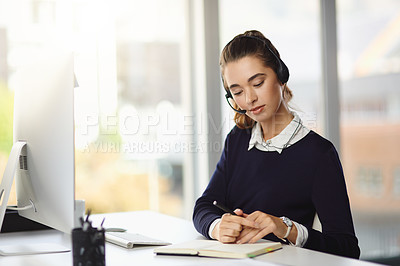 Buy stock photo Shot of an attractive young businesswoman wearing a headset and writing notes at her desk in a modern office