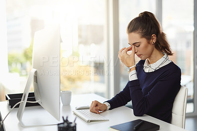 Buy stock photo Shot of an attractive young businesswoman sitting at her desk and feeling stressed in a modern office