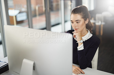 Buy stock photo Shot of an attractive young businesswoman sitting at her desk and looking at her computer screen in a modern office