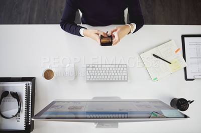 Buy stock photo Aerial shot of an unrecognizable young businesswoman sitting at her desk and using her cellphone in a modern office