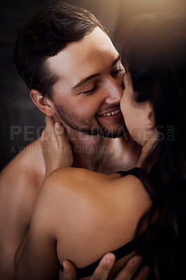Buy stock photo Shot of an affectionate young couple sharing an intimate moment at home