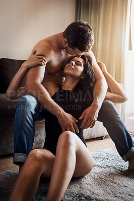 Buy stock photo Shot of an affectionate young couple embracing while relaxing in their living room at home