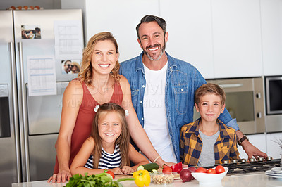 Buy stock photo Shot of a happy young family cooking together at home