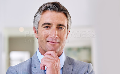 Buy stock photo Headshot of a confident mature man wearing a suit and standing indoors with his hand raised to his chin