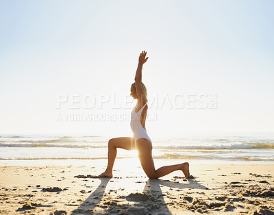 Buy stock photo Full length shot of an attractive young woman doing yoga early in the morning on the beach