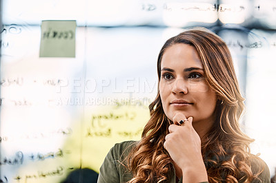 Buy stock photo Shot of an attractive young businesswoman planning and writing notes on a glass wall in her office at work