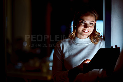 Buy stock photo Shot of a young businesswoman using a digital tablet during a late night at work