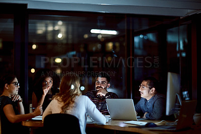 Buy stock photo Shot of a group of young businesspeople having a late night meeting at work
