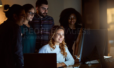 Buy stock photo Shot of a group of young businesspeople using a computer during a late night at work