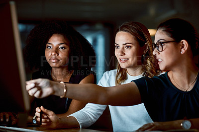 Buy stock photo Shot of a group of young businesswomen using a computer during a late night at work