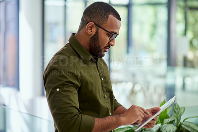Buy stock photo Cropped shot of a handsome middle aged  businessman working on a digital tablet in his office