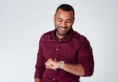 Buy stock photo Studio portrait of a confident young businessman looking at his wrist watch while standing against a grey background