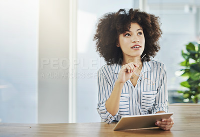 Buy stock photo Shot of an attractive young businesswoman looking thoughtful while using a digital tablet in her office