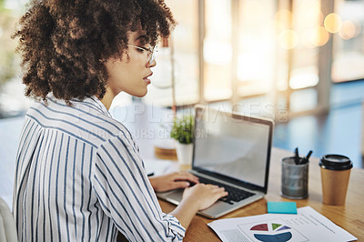 Buy stock photo Shot of an attractive young businesswoman working on a laptop in her office