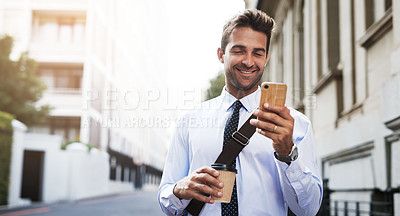 Buy stock photo Shot of a handsome young businessman texting on his cellphone while heading to work in the morning