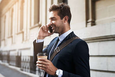 Buy stock photo Shot of a handsome young businessman talking on his cellphone while heading to work in the morning