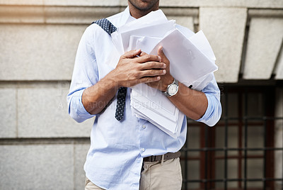 Buy stock photo Shot of an unrecognizable young man holding a heap of paper documents while walking to work in the morning