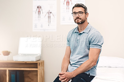 Buy stock photo Portrait of a handsome mature male physiotherapist sitting in his office