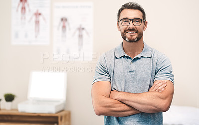 Buy stock photo Portrait of a handsome mature male physiotherapist posing with his arms folded in his office