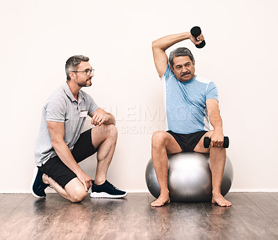 Buy stock photo Full length shot of a senior man exercising with dumbbells during a rehabilitation session with his physiotherapist