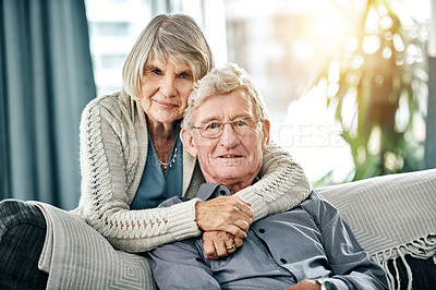 Buy stock photo Portrait of a happy elderly couple relaxing together on the sofa at home