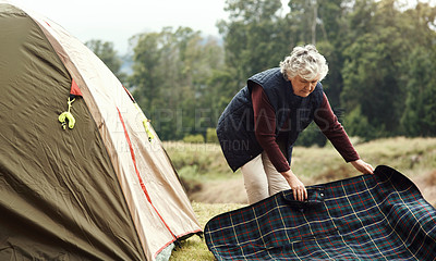 Buy stock photo Full length shot of a senior woman setting up a tent at her chosen camping spot
