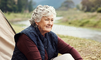 Buy stock photo Cropped shot of a senior woman sitting outside of a tent on her chosen camping spot
