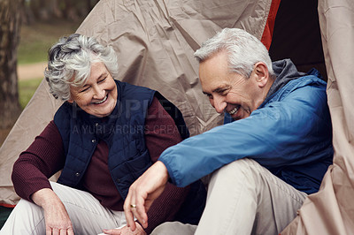 Buy stock photo Cropped shot of an affectionate senior couple relaxing at their chosen camping spot