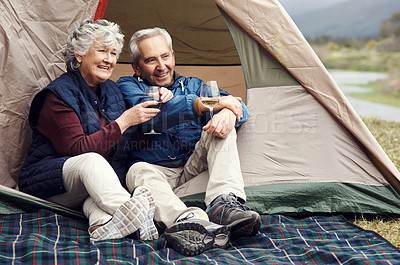Buy stock photo Full length shot of an affectionate senior couple enjoying wine while relaxing at their chosen camping spot