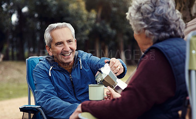 Buy stock photo Cropped shot of an affectionate senior couple enjoying coffee while relaxing at their chosen camping spot