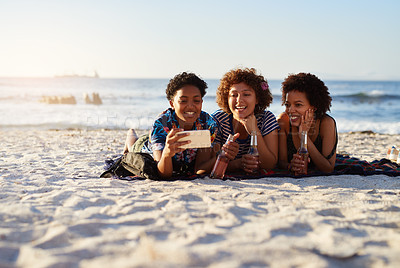 Buy stock photo Shot of an attractive young trio of women laying down on the beach and taking selfies together during the day