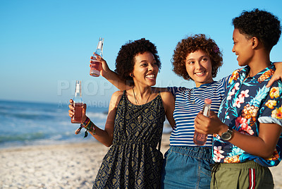 Buy stock photo Shot of three attractive young women standing and holding each other on the beach during the day