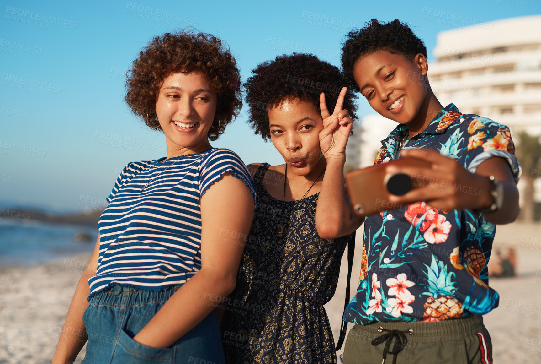 Buy stock photo Shot of three attractive young women laying down on the beach and taking selfies together during the day