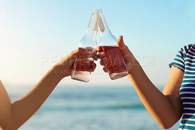 Buy stock photo Shot of two unrecognizable young women celebrating and having a drink together on the beach during the day