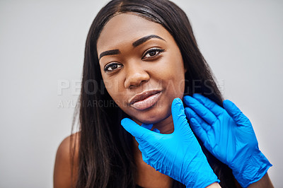 Buy stock photo Shot of a beautiful young woman getting her face analyzed  by gloved hands against a grey background